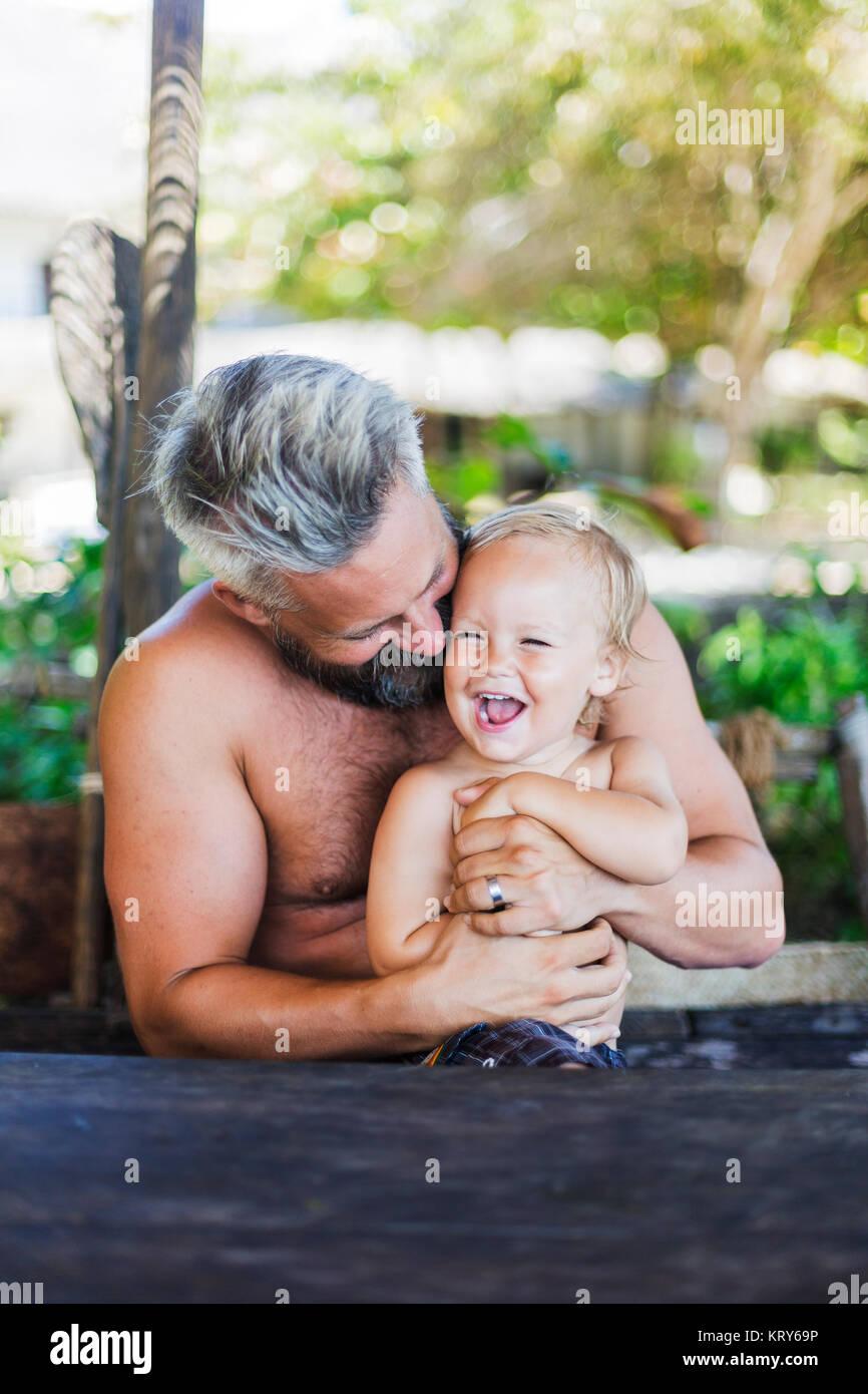 Metà uomo adulto seduto con suo figlio a Diani Beach, Kenya Foto Stock