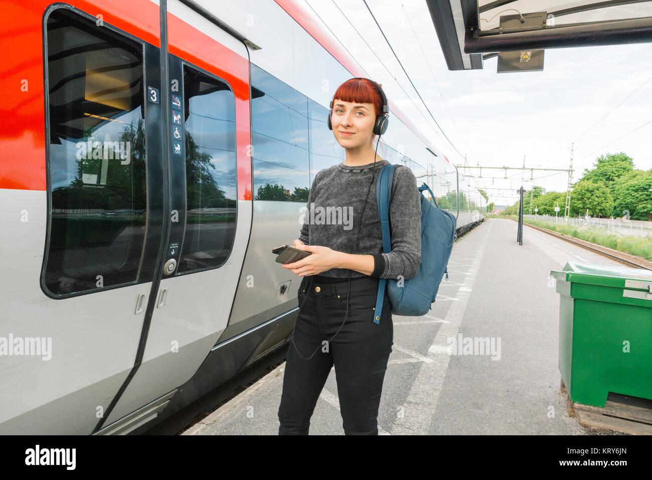 Donna che indossa le cuffie sulla piattaforma del treno Immagini Stock