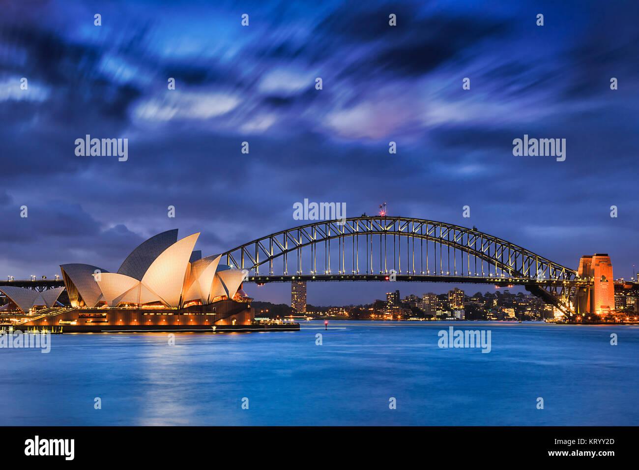 Sydney, Australia, 18 marzo 2017: famosa Sydney Opera House e Harbour Bridge al tramonto. Nuvole sfocata e luci Immagini Stock