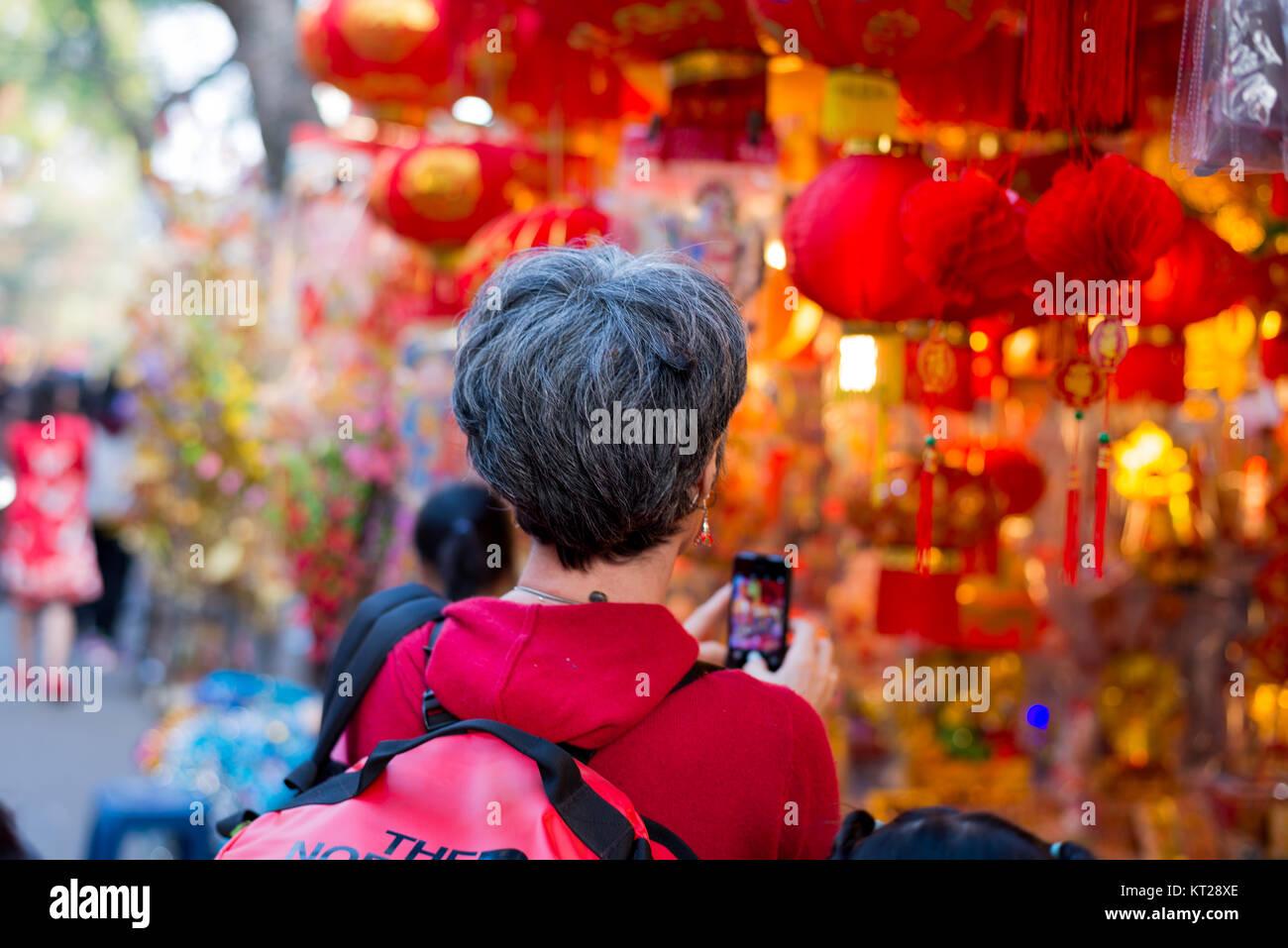 Una donna fotografo in Hanoi Old Quarter quando il nuovo anno lunare Immagini Stock