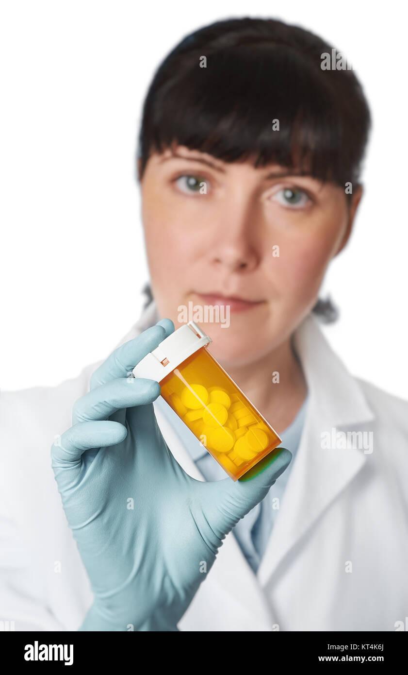 Donne medico o infermiere con il giallo un vasetto di pillole in mano su sfondo bianco. DOF poco profondo, concentrarsi sulle pillole Foto Stock