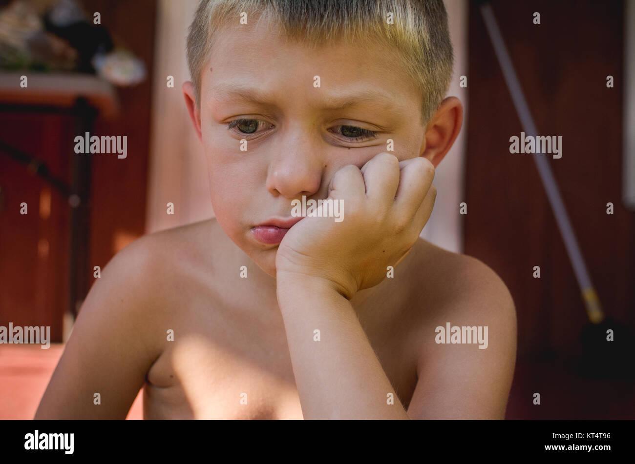 Un giovane ragazzo che guarda triste. Foto Stock