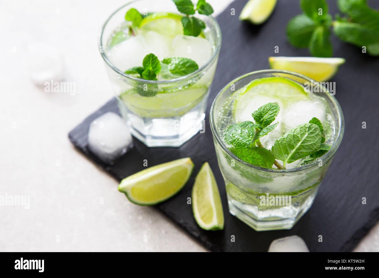 Il freddo estivo rinfrescante limonata mojito in un bicchiere su una scheda di ardesia e pietra dello sfondo. Immagini Stock