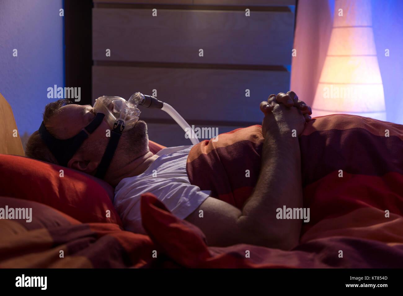 Un uomo con sindrome da apnea nel sonno, indossa una maschera CPAP durante il sonno, una maschera per la respirazione Immagini Stock