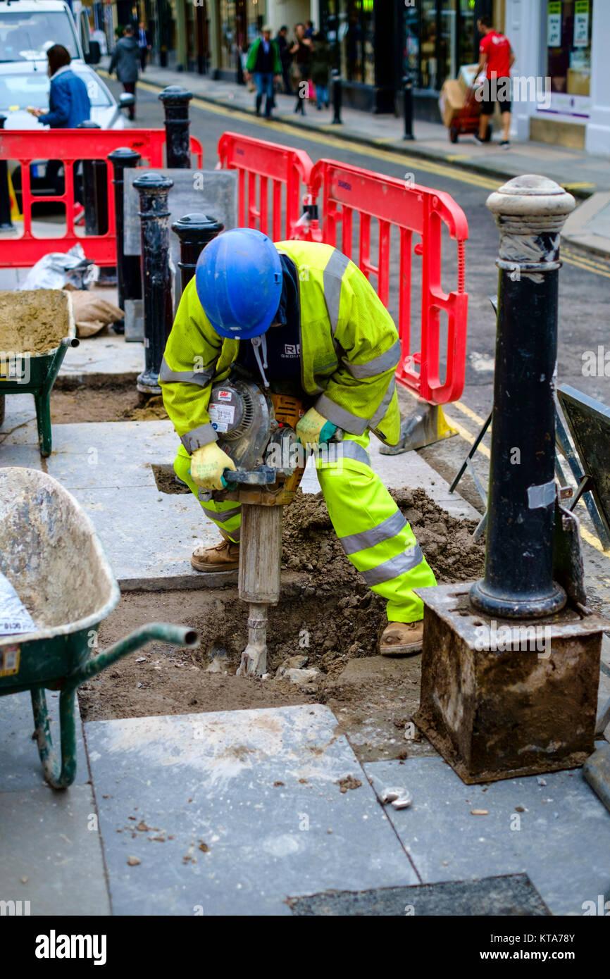 Un uomo di scavare un buco in strada. Immagini Stock