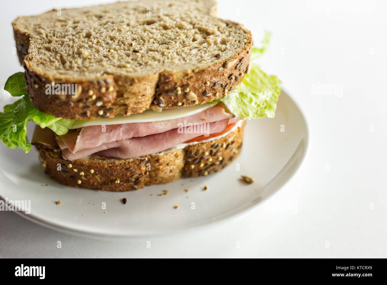 Panino di prosciutto fatto con pane artigianale su una piastra bianca. Copia dello spazio. Sfondo bianco. Immagini Stock