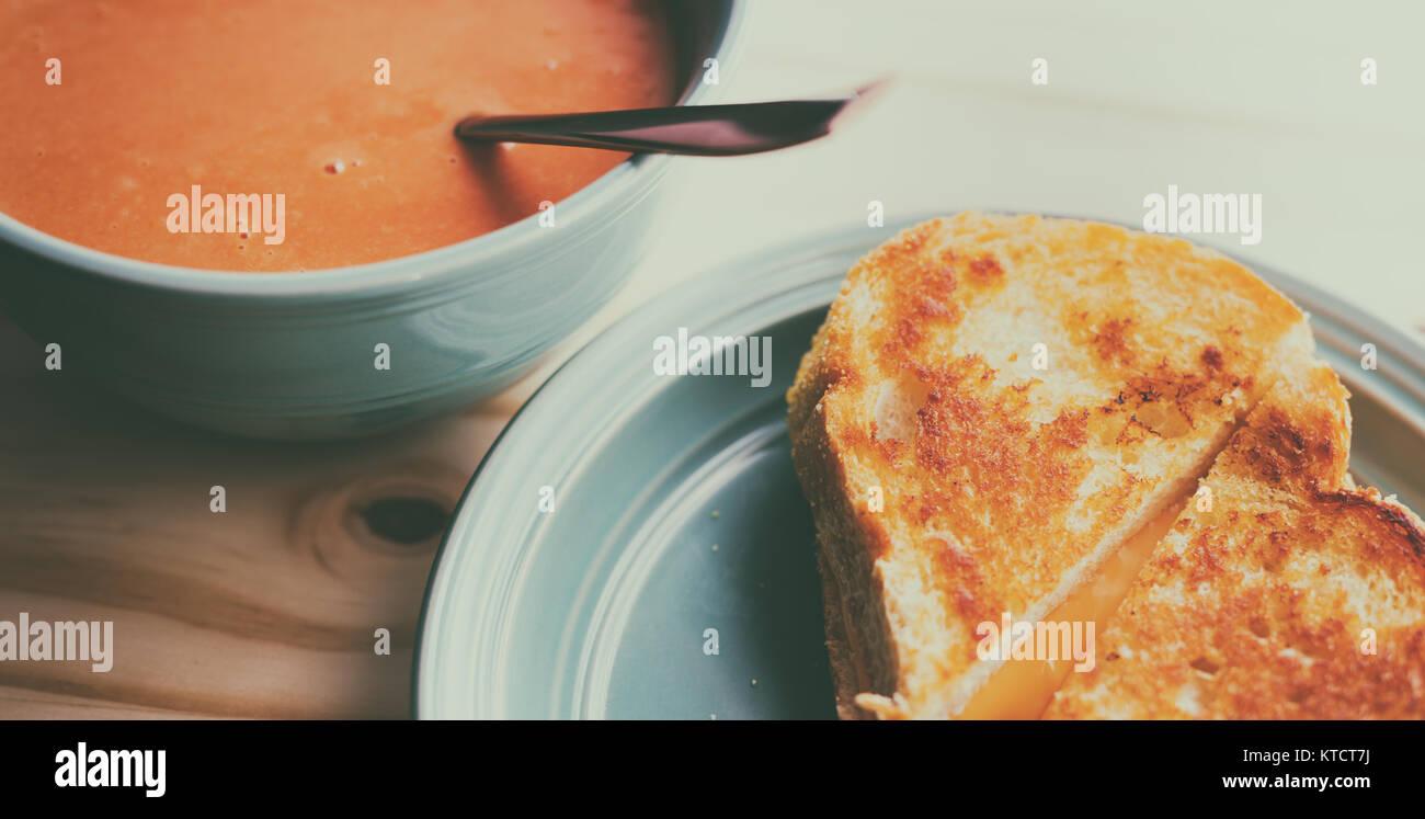 Formaggio alla griglia in sandwich con una ciotola di calda zuppa di pomodoro. Foto Stock