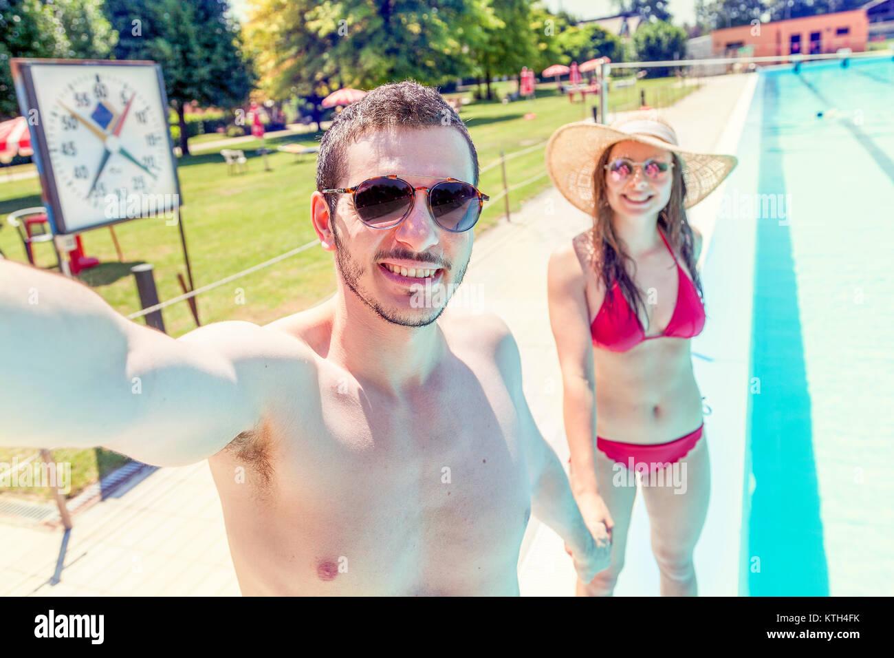 Giovane coppia amorevole accanto alla piscina prende un selfie in costume da bagno. Concetto di giovani divertirsi Immagini Stock