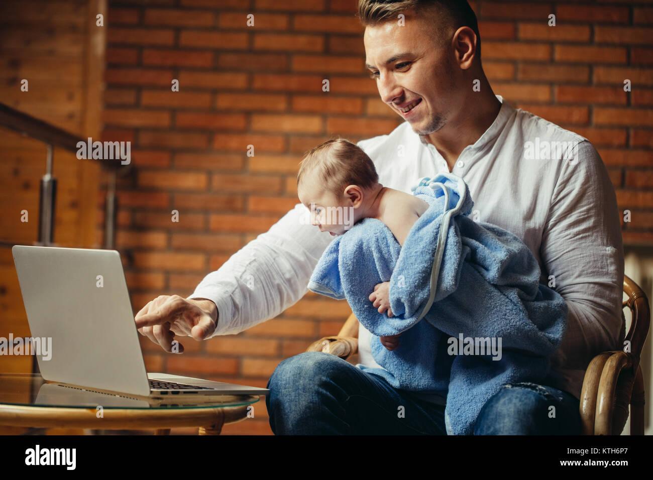 Padre con il neonato a lavorare da casa utilizzando Laptop Immagini Stock