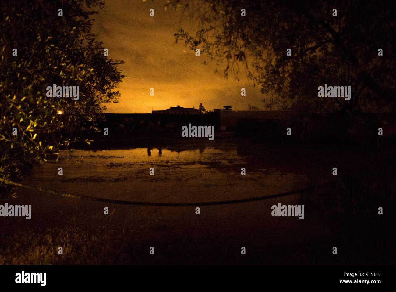 Vista notturna dalla strada di un invaso il campo dopo una pioggia pesante nella campagna toscana. Sullo sfondo Immagini Stock