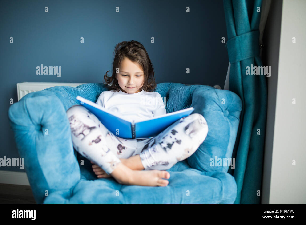 Funny happy toddler girl leggendo un libro e giocare a letto. Bambini giocano in casa. Vivaio bianco. Bambino in Immagini Stock