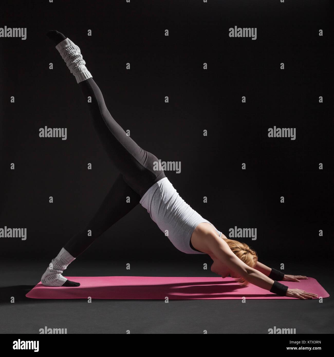Giovane donna a praticare yoga, Eka Pada Adho Mukha Svanasana / One-Legged Downward-Facing cane pongono Immagini Stock
