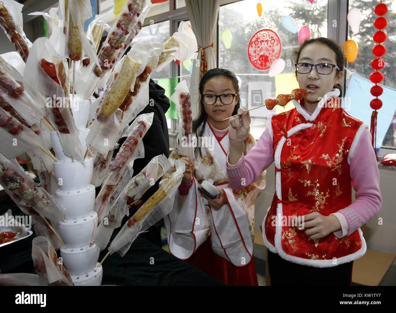 Pechino, Cina. 29 Dic, 2017. Gli studenti del gusto di frutta sugarcoated su un bastone, un popolare snack, durante Immagini Stock
