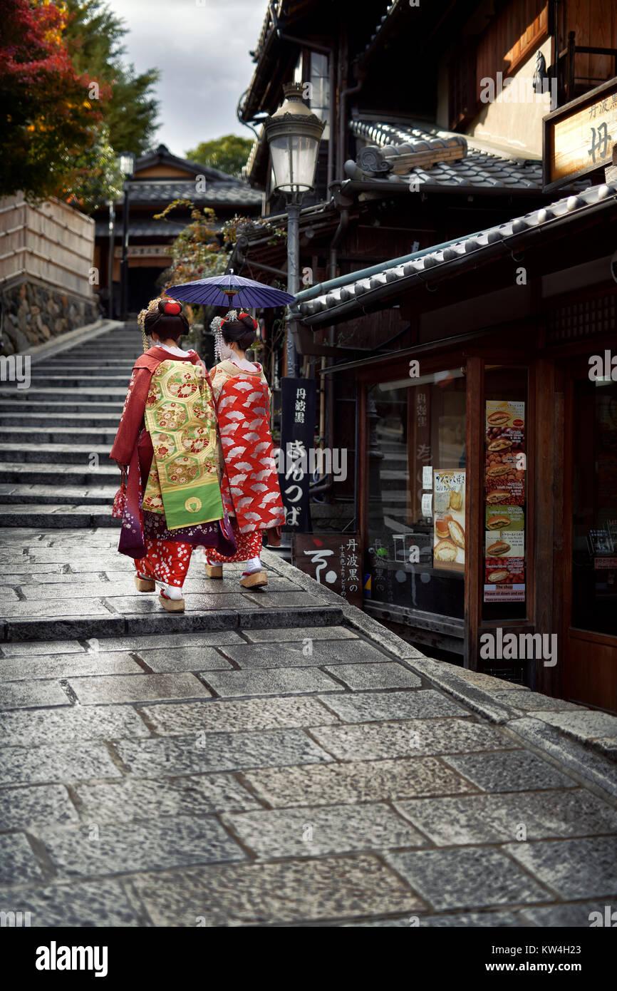 Due Maiko, Geisha apprendisti in splendidi kimono colorati con lunghi intricato obi a piedi con un ombrellone su Immagini Stock