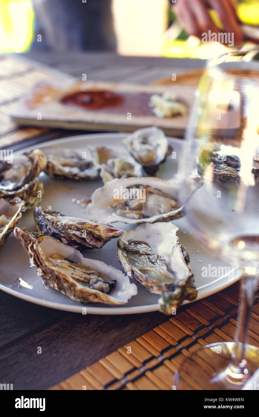 Piatti a base di frutti di mare e un bicchiere di vino. Immagini Stock