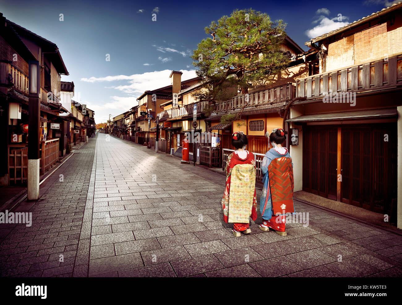 Due Maiko, Geisha apprendisti in splendidi kimono colorati con obi lunghe passeggiate lungo vuoto Hanamikoji Dori Immagini Stock