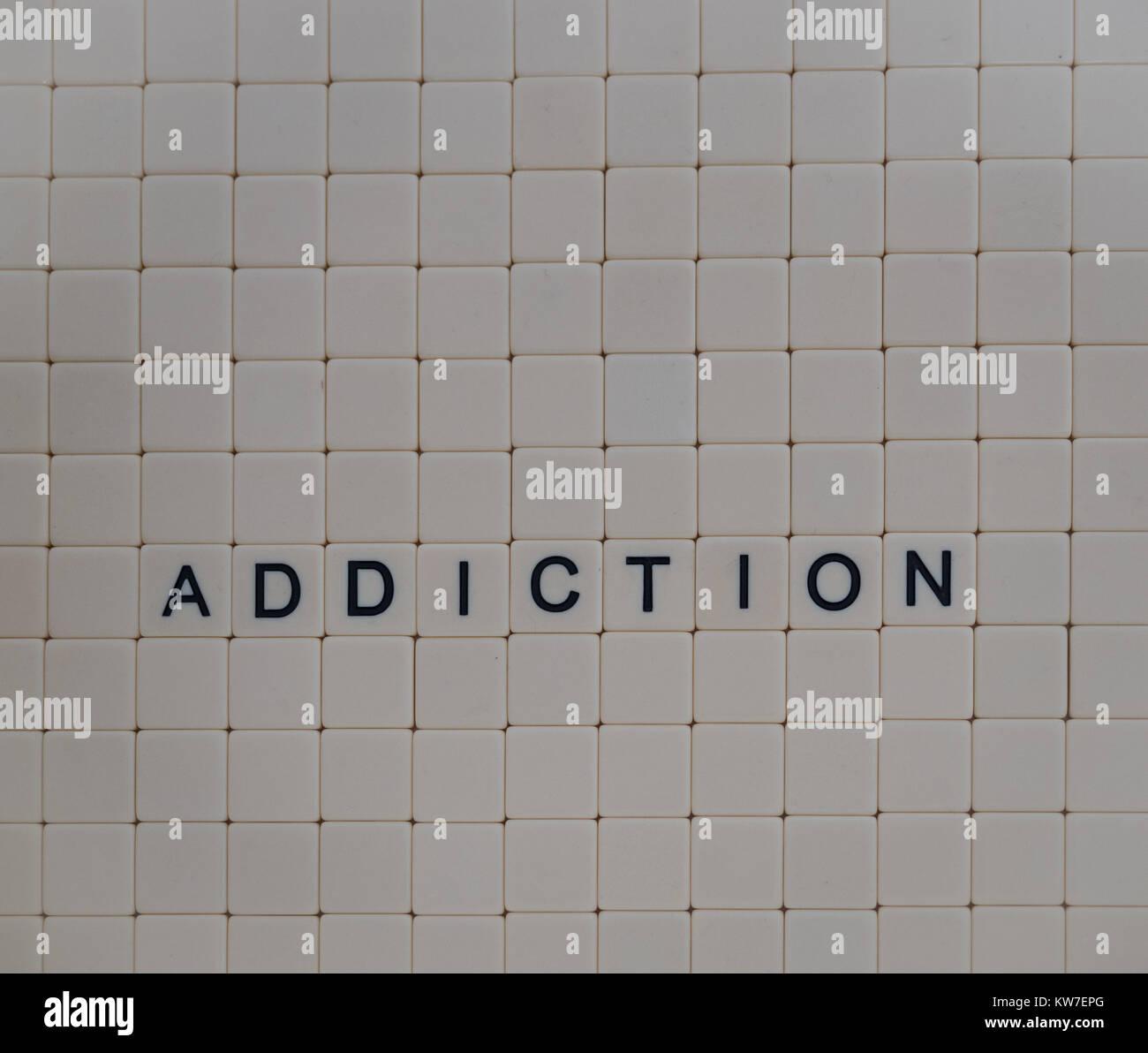 Addiction scritto in lettere maiuscole nere su mattonelle beige con uno sfondo di piastrelle bianche. Fotografato Immagini Stock