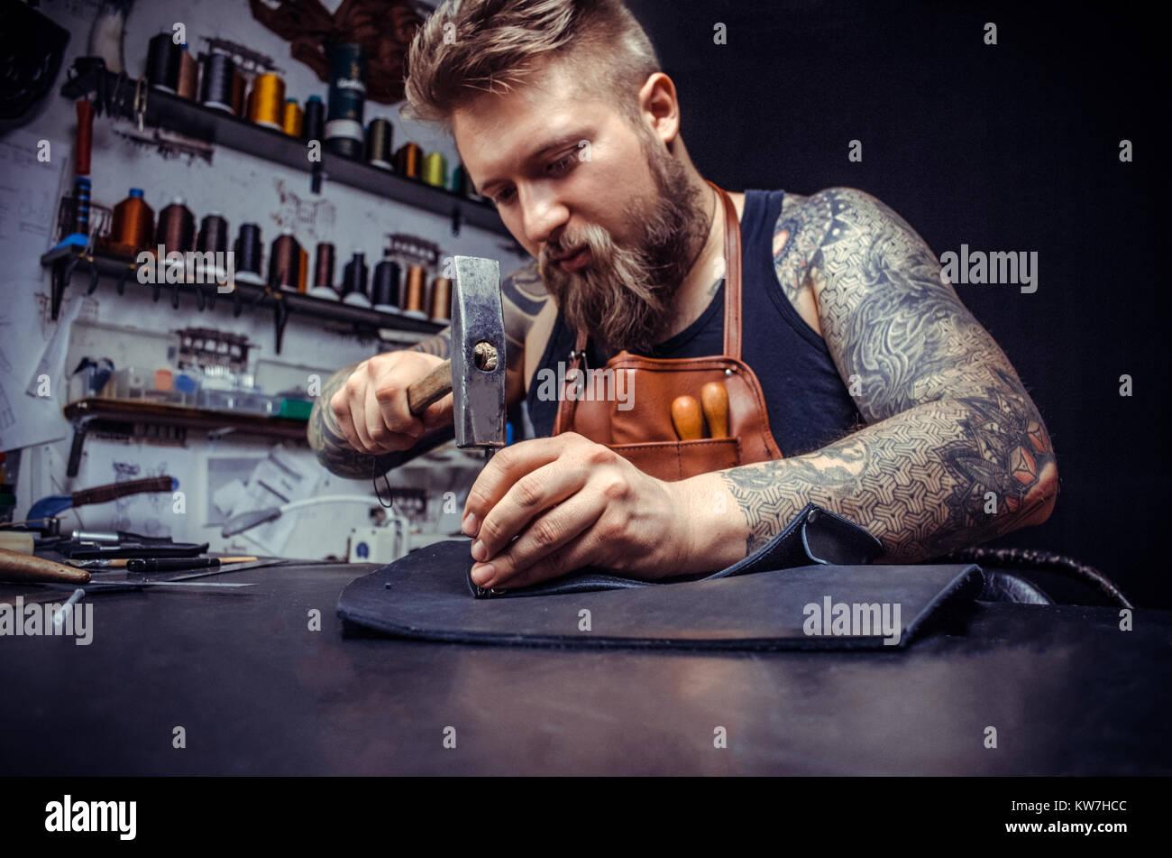 Close up di un calzolaio uomo che lavora con cuoio utilizzando gli strumenti di creazione Immagini Stock