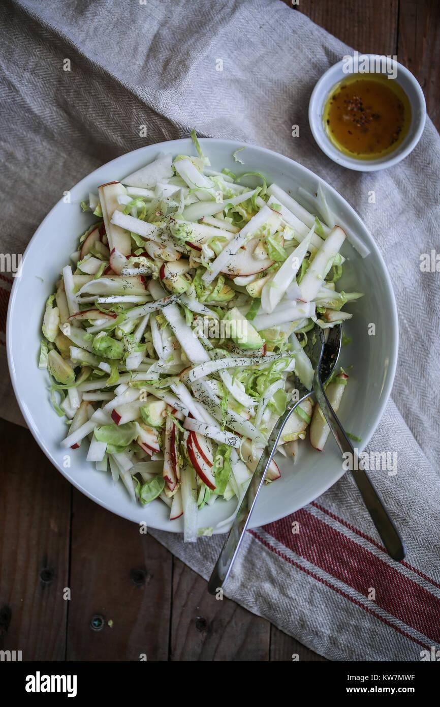 Fresco e salutare vegan insalata con finocchio, Bruxelles germoglio, mele, sedano rapa bianca. Con la citronette Immagini Stock