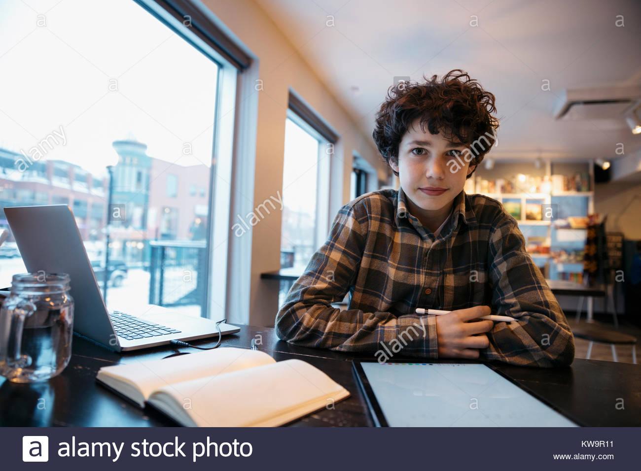 Ritratto fiducioso di alta scuola ragazzo studente,utilizzando lo stilo con tavoletta digitale in cafe Immagini Stock