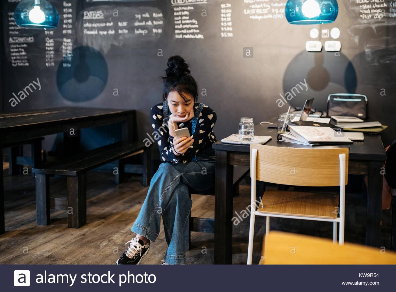 Asian tween girl texting con smart phone al cafe tabella Immagini Stock