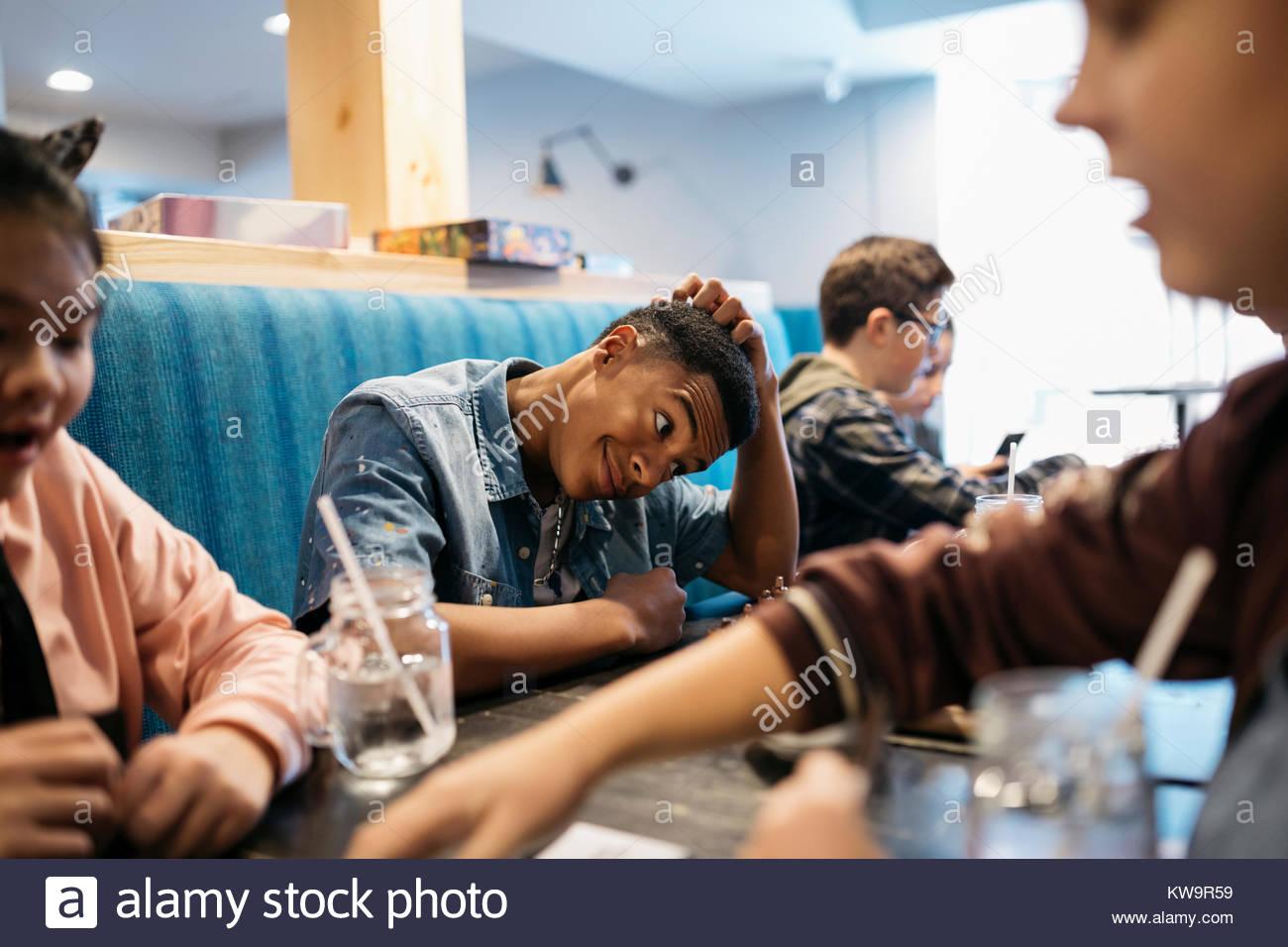 Tween ragazzo giocando con un amico al tavolo del bar Immagini Stock