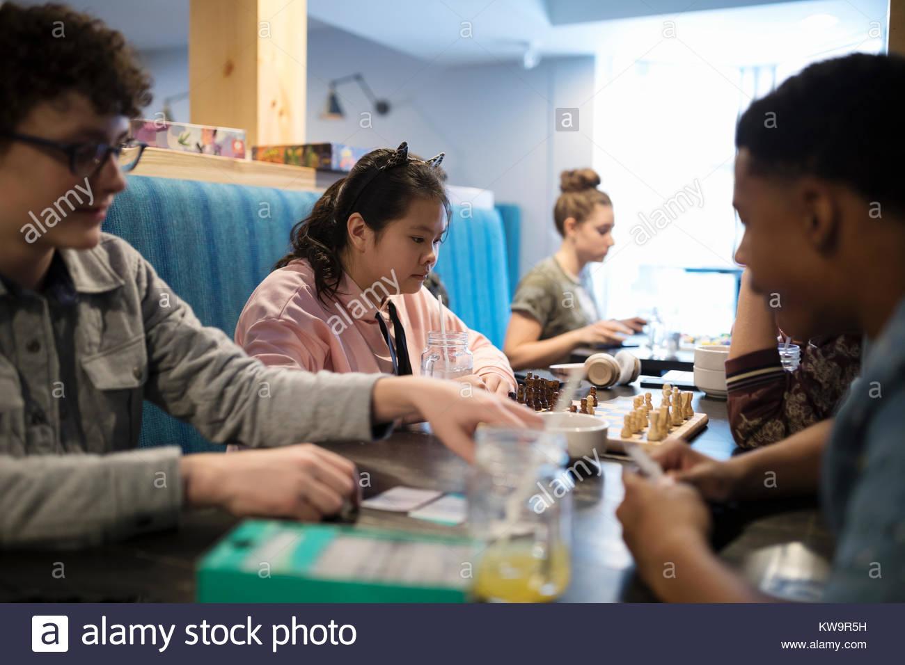 Focalizzato Asian tween girl giocando a scacchi con un amico al tavolo del bar Immagini Stock