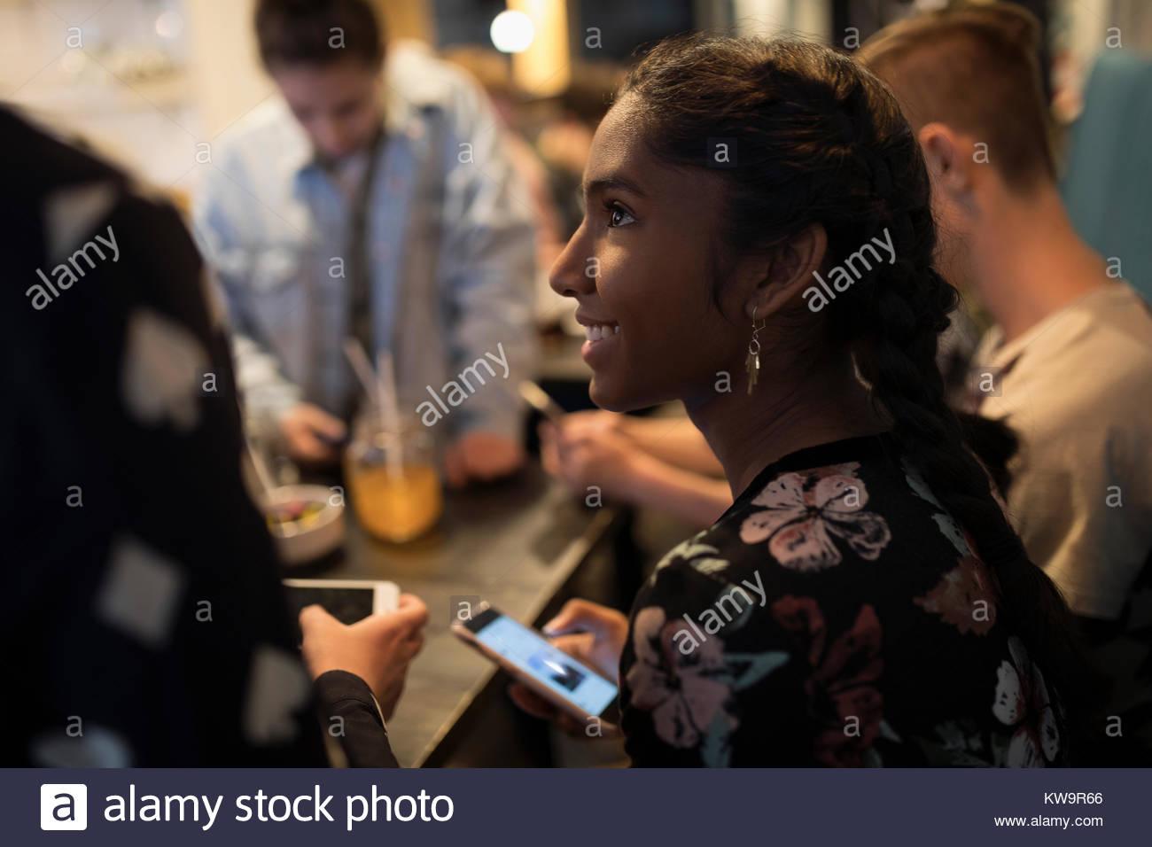 Indiano sorridente ragazza tween texting con smart phone,appendere fuori al cafe tabella Immagini Stock