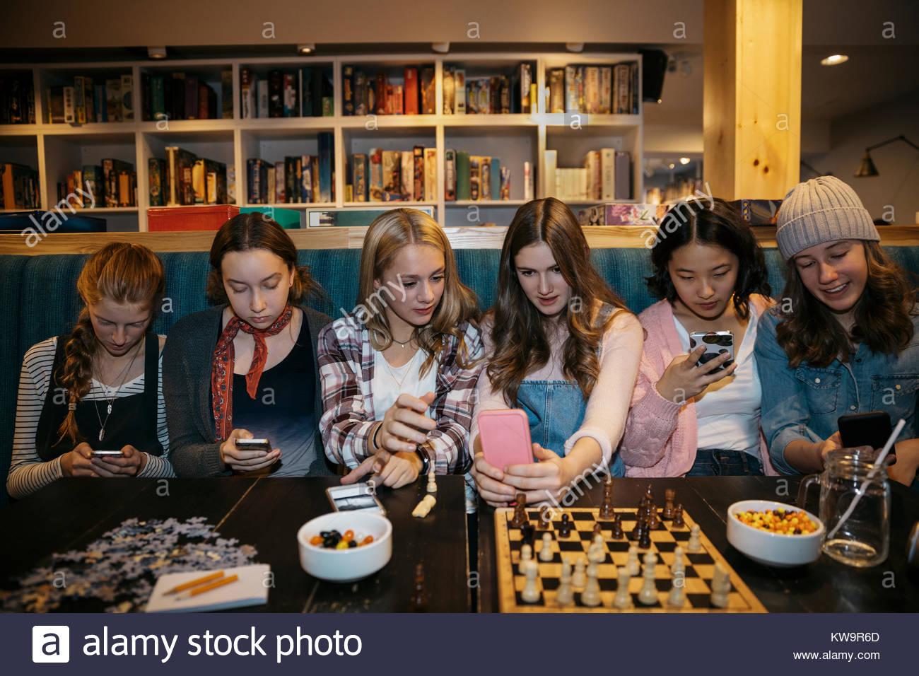 Tween girl amici seduti in una fila,invio messaggi con i telefoni intelligenti e giocare a scacchi al cafe tabella Immagini Stock
