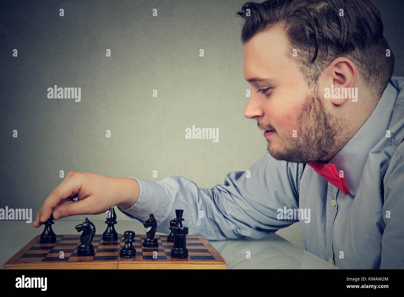 Giovane uomo chunky concentrata sulla strategia di costruzione mentre gioca a scacchi. Immagini Stock