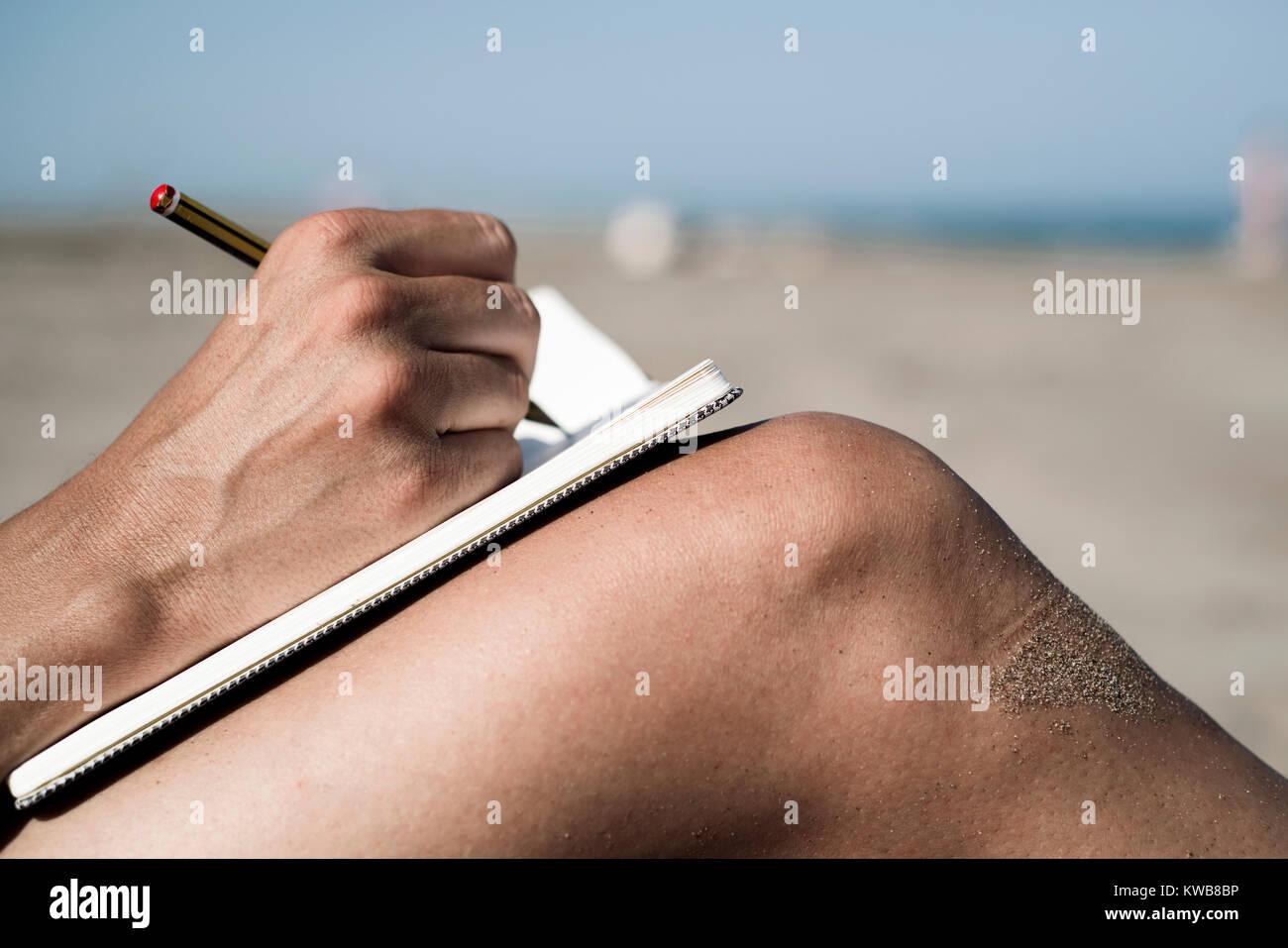 Primo piano di un giovane uomo caucasico scrivere con una penna in un notebook sulle sue gambe rasata, sulla spiaggia Immagini Stock