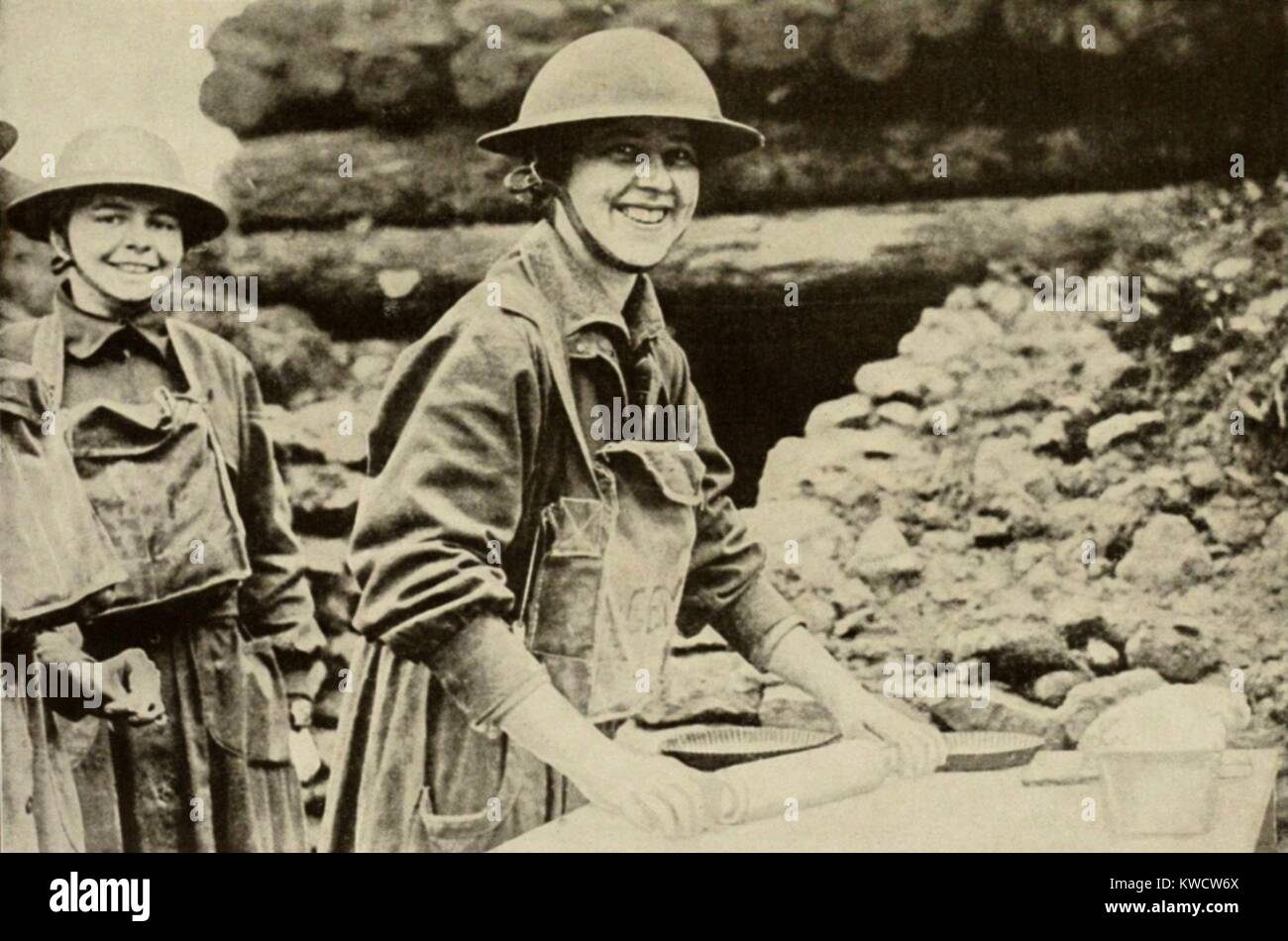 Guerra mondiale 1. American Esercito della Salvezza ragazze, con le maschere antigas appesa al collo, fare torte Immagini Stock