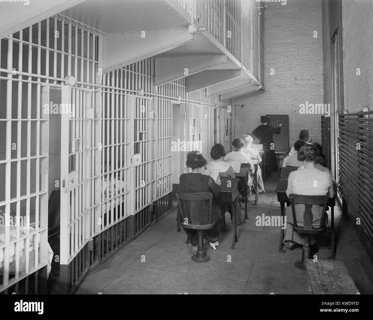 Le giovani donne a scrivanie in una prigione americana c. 1920. Vestito in abiti di strada, si siedono in due file Immagini Stock