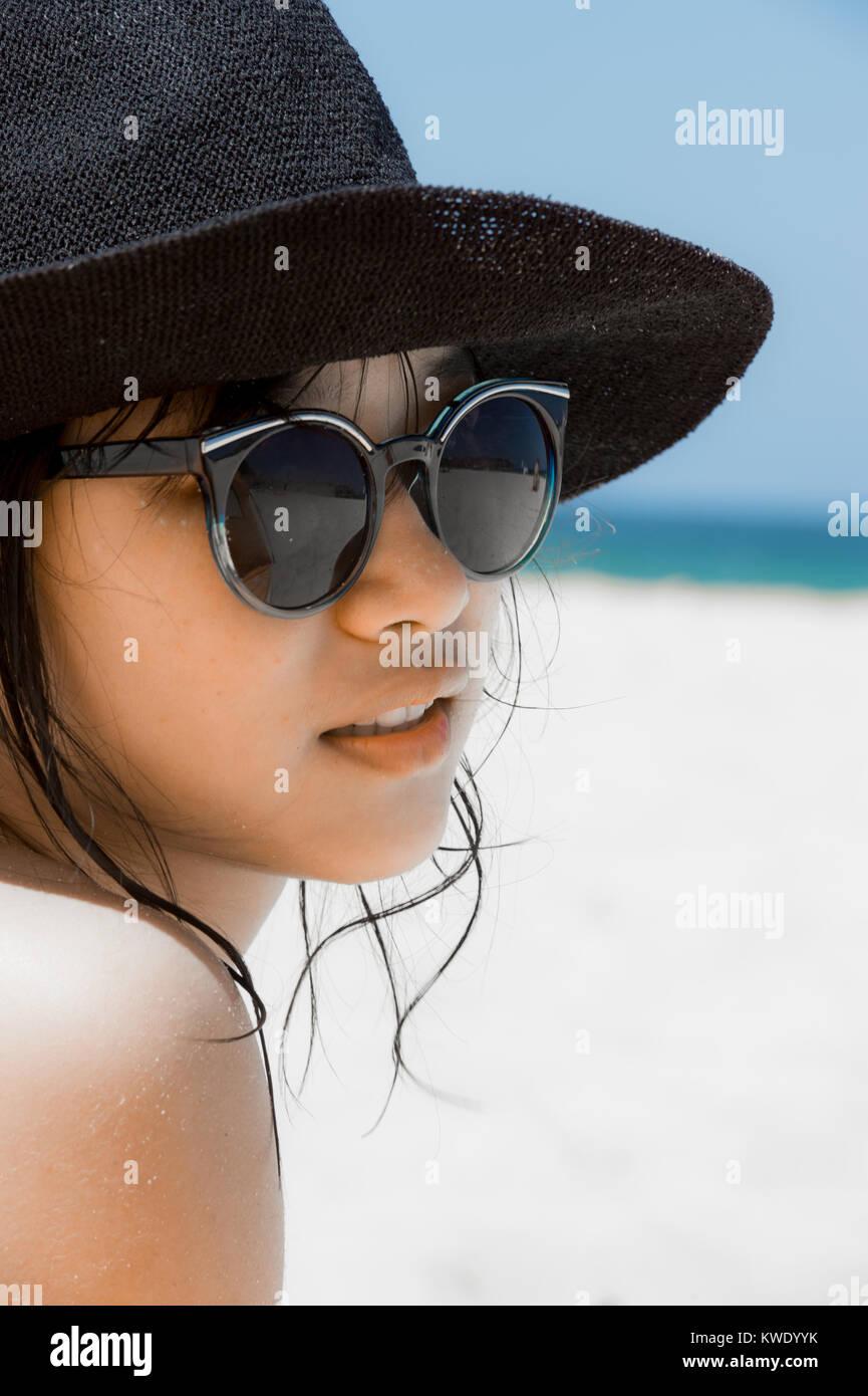 52396046114ddd Bellissima ragazza con occhiali da sole e cappello indietro sdraiato sulla  spiaggia in un bikini