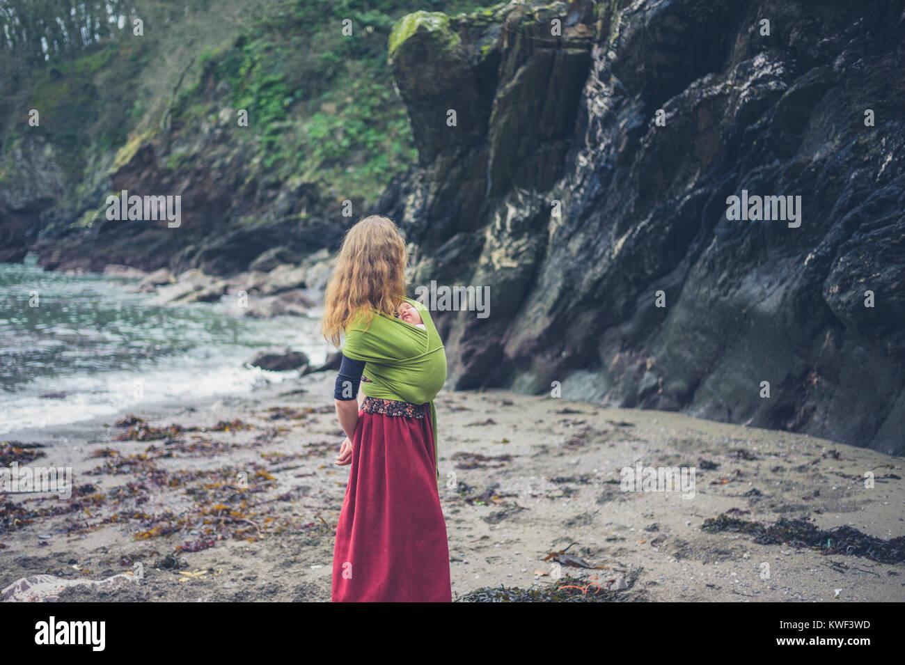 Una giovane madre è sulla spiaggia con il suo bambino in una imbracatura Immagini Stock