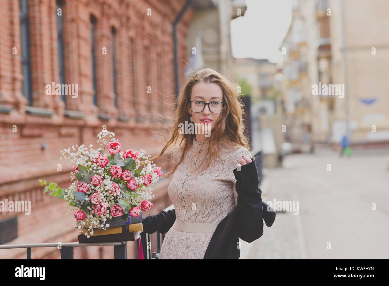 76a79c6c7dde Un felice ragazza in abito di lacy tenendo un mazzo di fiori e un pacco di