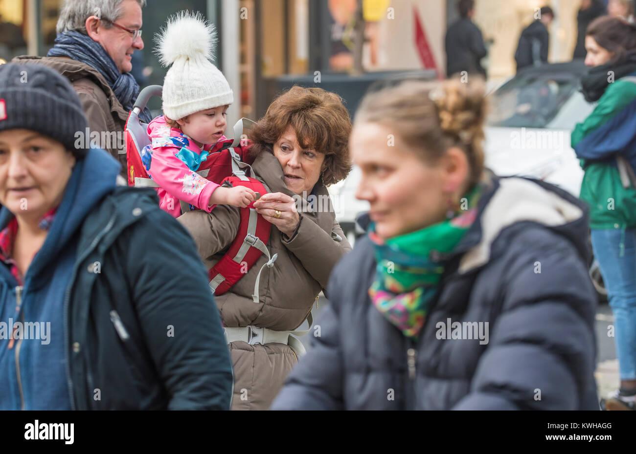 Donna di trasportare un bambino sulle sue spalle, una piggy back ride, tra la folla in una strada trafficata in Immagini Stock