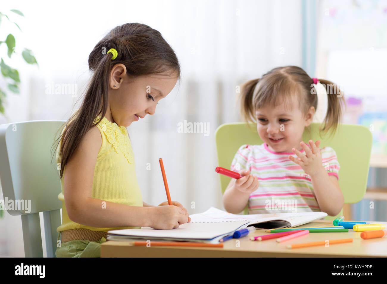 Dei bambini felici disegno nella nursery room Immagini Stock