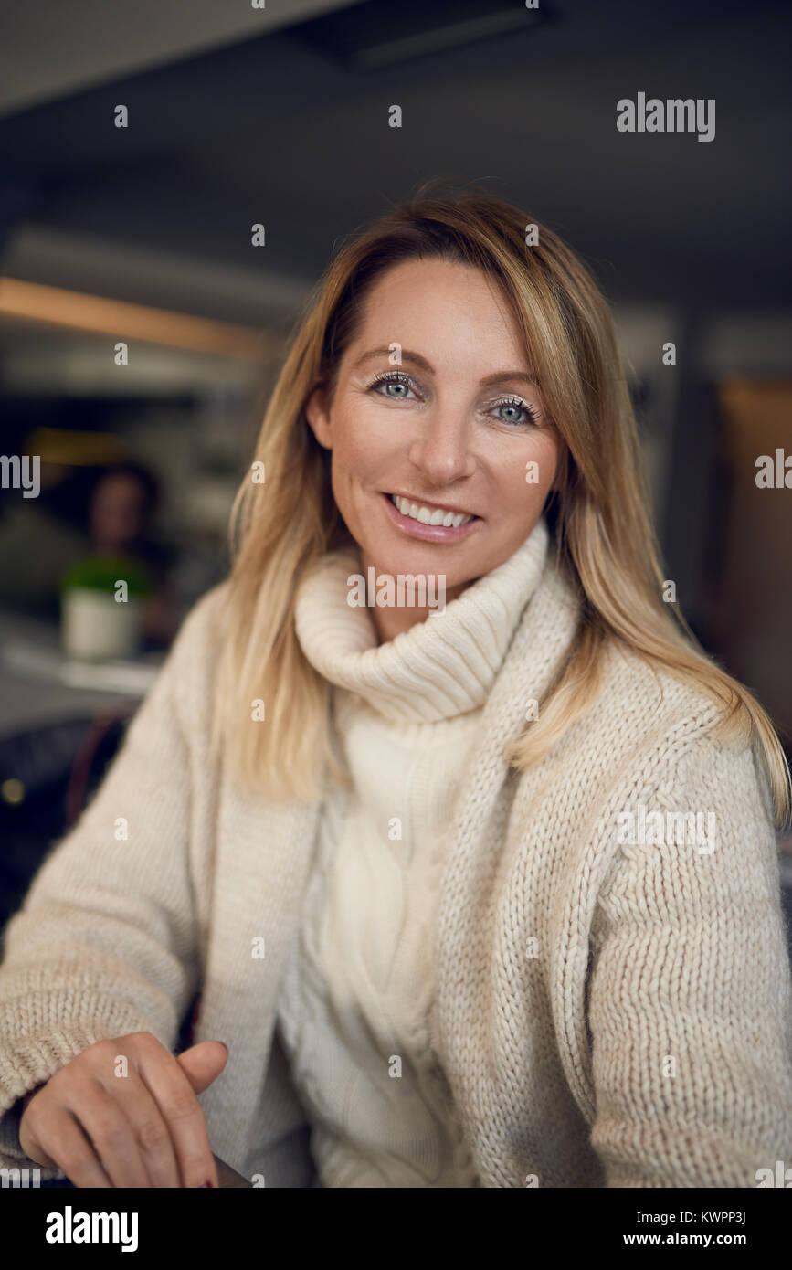 Attraente donna bionda sorridente alla telecamera mentre sorseggiate un bicchiere di vino al chiuso in un pub o Immagini Stock
