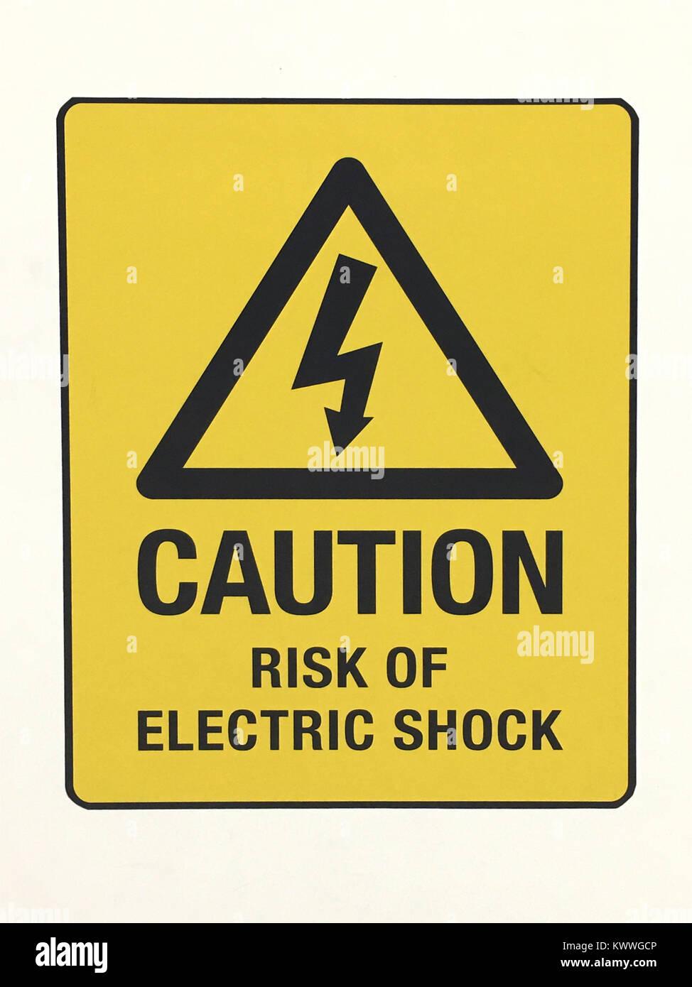 Attenzione gialla di avvertimento di segno per il rischio di scosse elettriche Immagini Stock