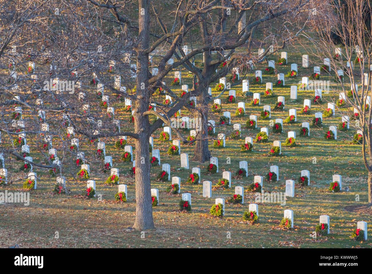 ARLINGTON, VA/STATI UNITI D'America - 1 gennaio 2018: raggi del caldo sole del pomeriggio risplenda su ghirlande con centine rosso che ornano lapidi che commemora la vita di Bra Foto Stock