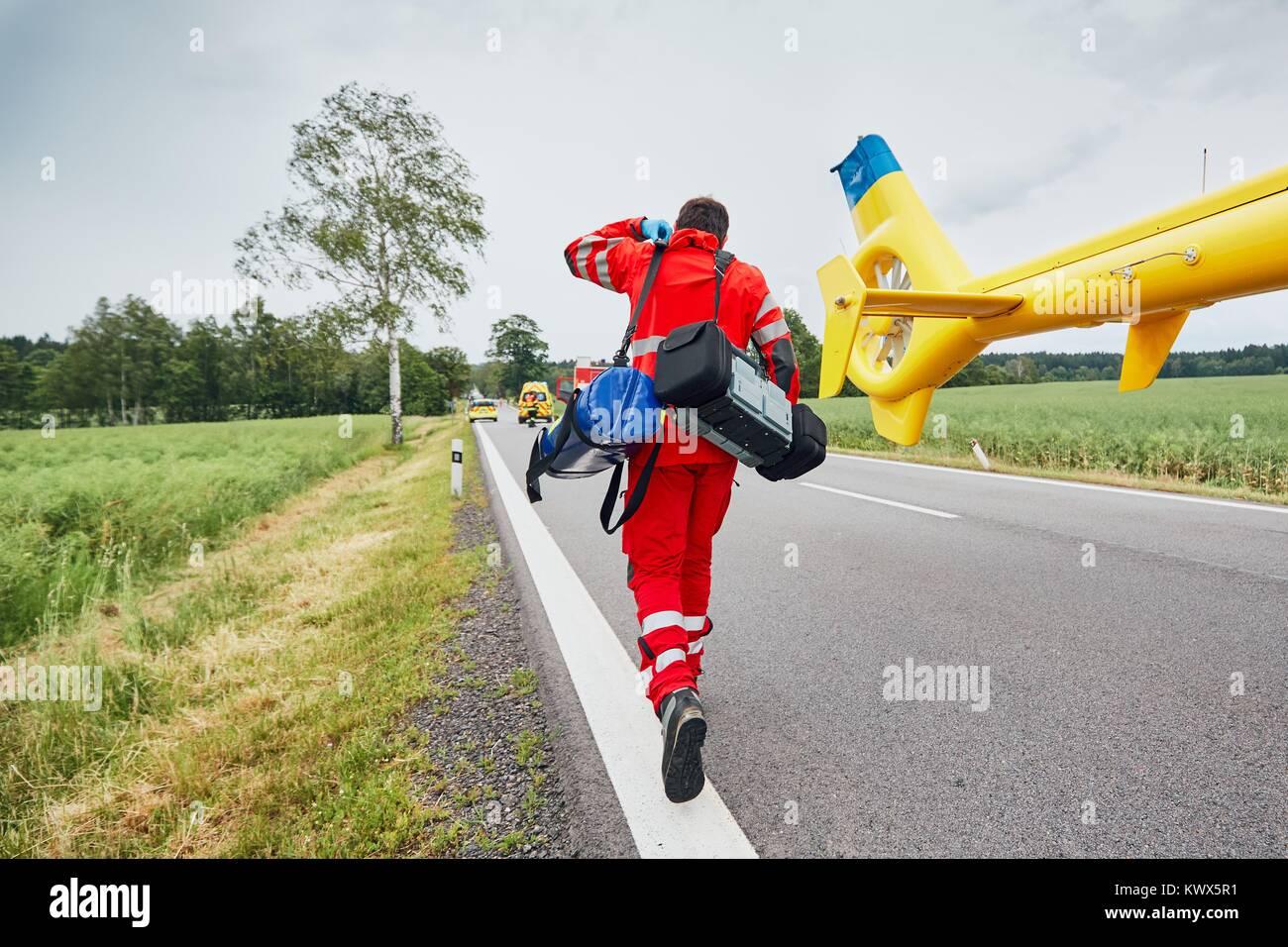 Medico con defibrillatore e altre apparecchiature in esecuzione da un elicottero. Team del servizio medico di pronto Immagini Stock