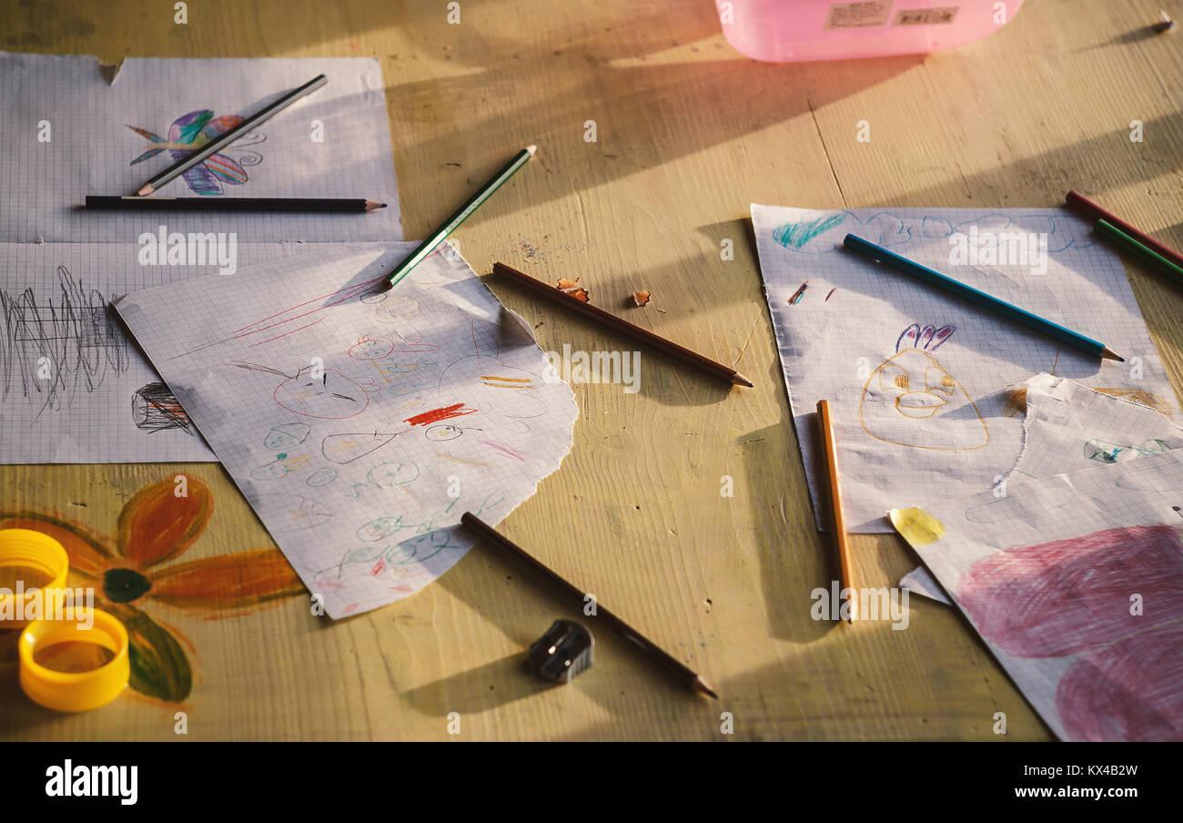 Varie kid's disegni su carta e accessori sul tavolo. Foto Stock