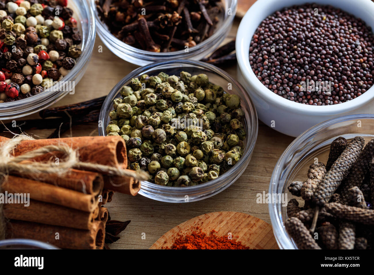 Il pepe verde e altre spezie su una superficie in legno Immagini Stock