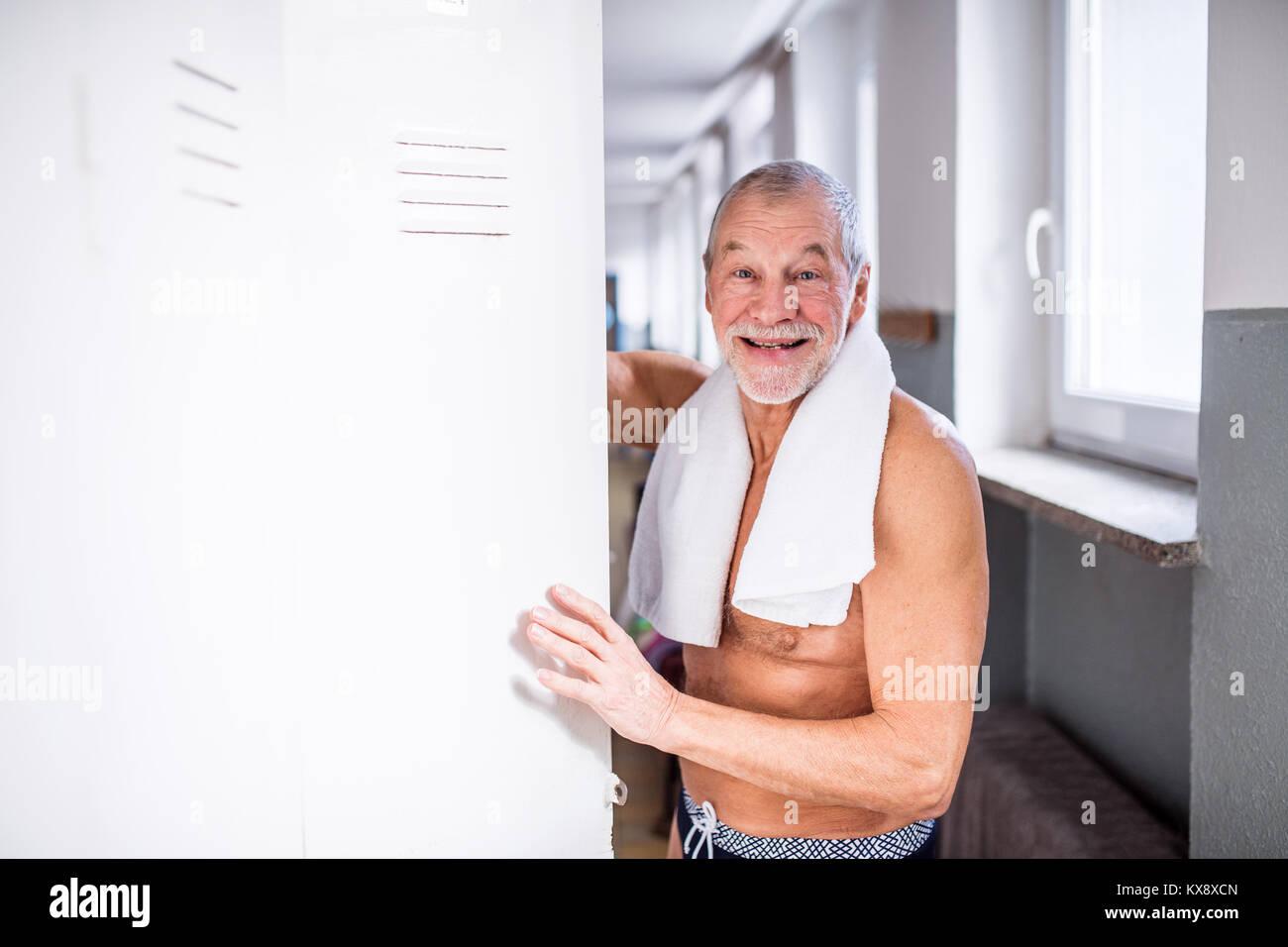 Senior man standing dagli armadietti in una piscina al coperto. Immagini Stock