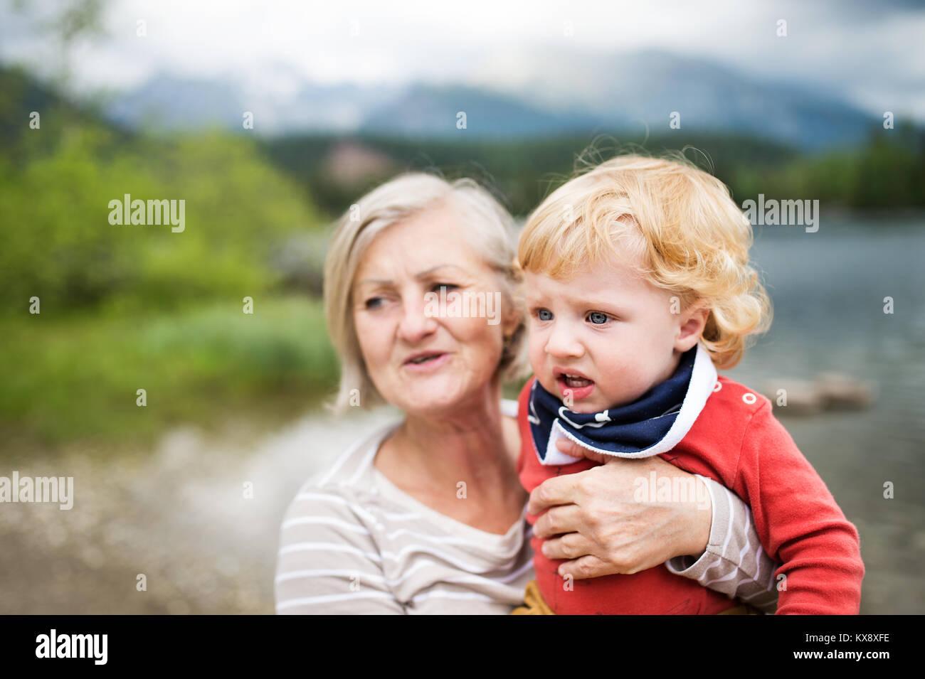 Senior Donna con bambino al lago, giorno d'estate. Immagini Stock