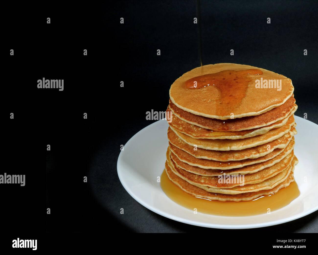 Pila di freschi fatti in casa pancake con sciroppo d'acero servita su piastra bianca, sfondo nero con spazio Immagini Stock
