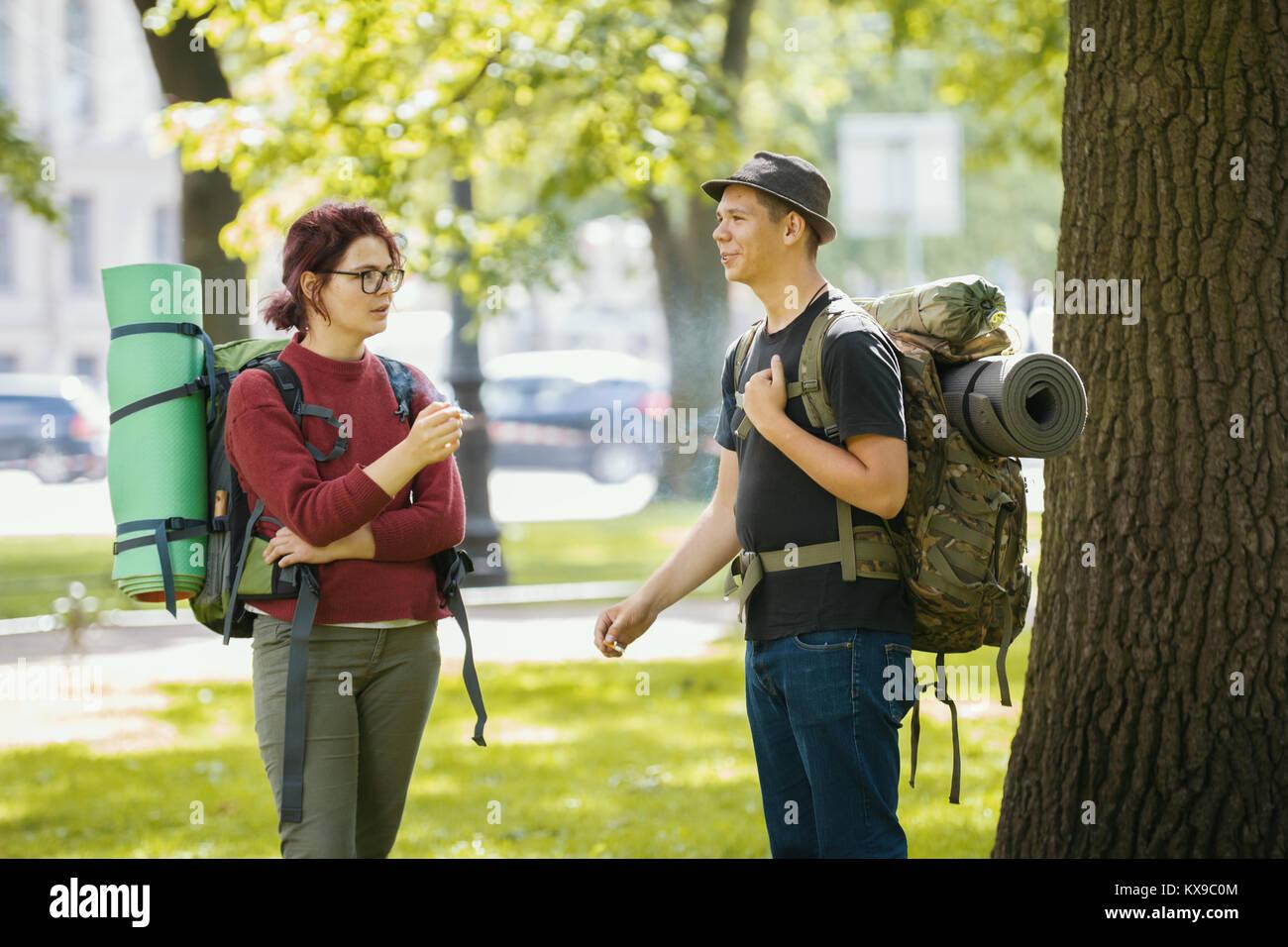 Gli adolescenti i turisti con zaini - fumatori e in piedi nel parco in estate mezzogiorno Immagini Stock