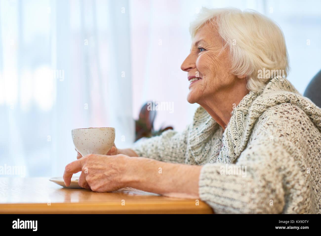 Senior donna con la tazza di caffè fragrante Immagini Stock