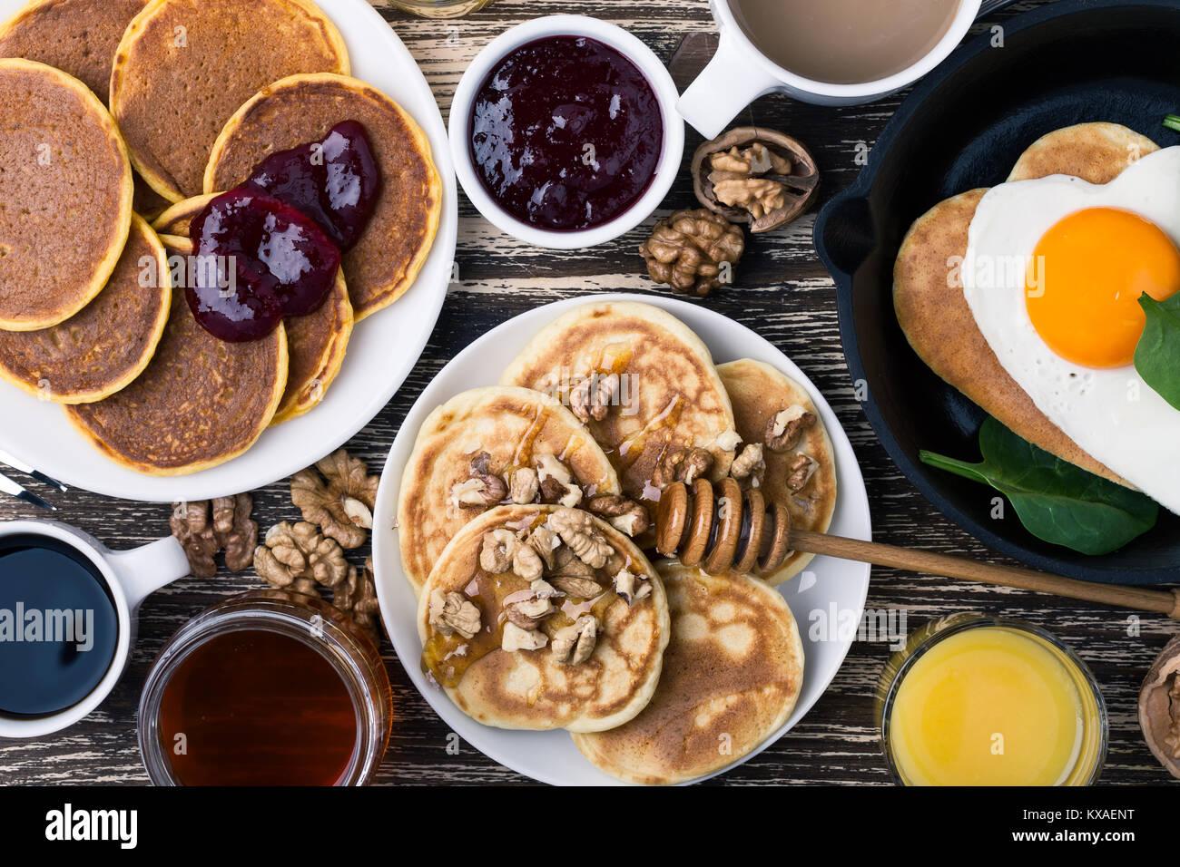 Il giorno di San Valentino la colazione o il brunch. In casa forma di cuore uovo fritto e frittelle in padella in Immagini Stock
